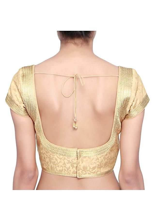 Beige brocade blouse enhanced in gold lace only on Kalki