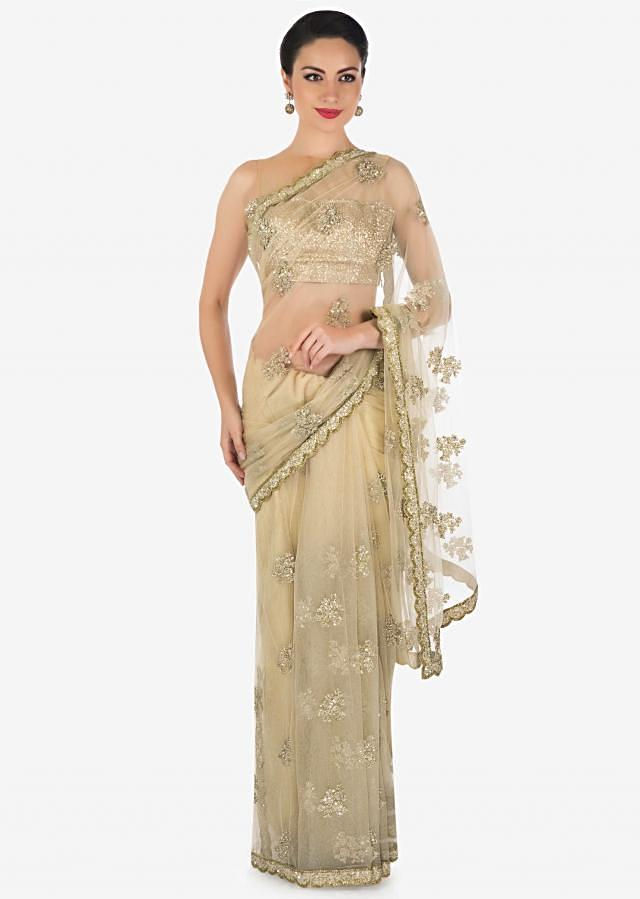 Beige saree in net with sequin and zari embroidered butti only on Kalki