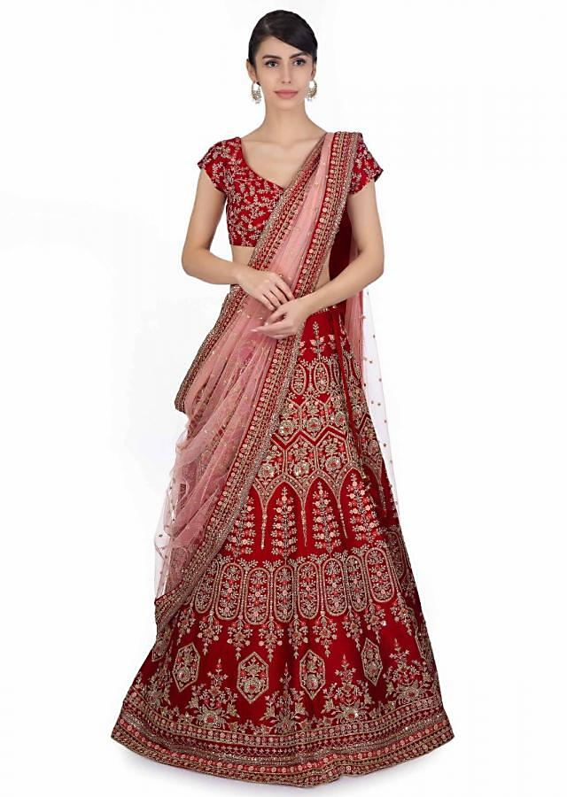 Blood red raw silk embroidered lehenga and blouse paired with powder pink net dupatta only on Kalki