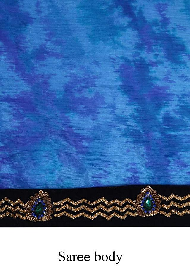 Blue shaded saree featuring in chiffon. Border is enhanced in kundan and sequin embroidery. Matched with ready blouse in navy blue velvet.