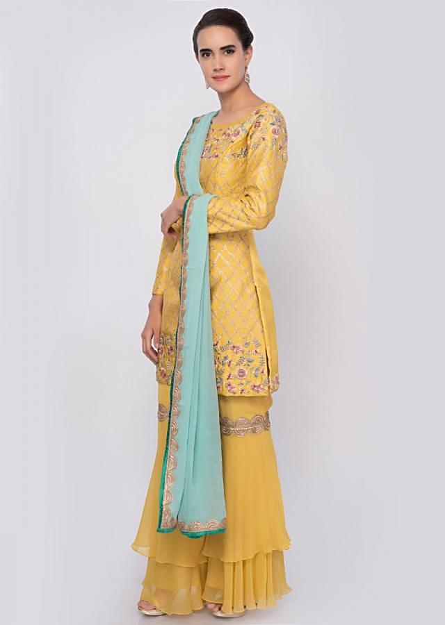Bright yellow sharara suit in multi color floral embroidery along with lace work only on Kalki