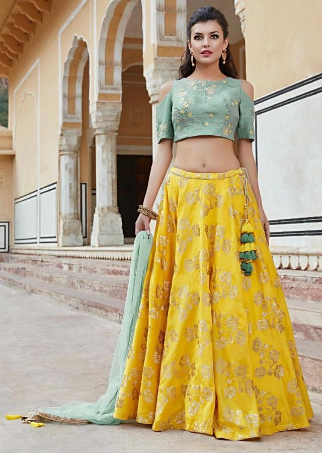 Bright yellow lehenga in silk with contrast blouse adorn in zari and resham work only on Kalki