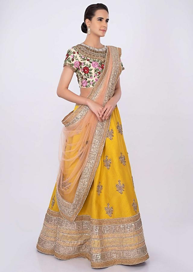 Chrome yellow raw silk lehenga with  cream blouse and pale pink net dupatta only on kalki