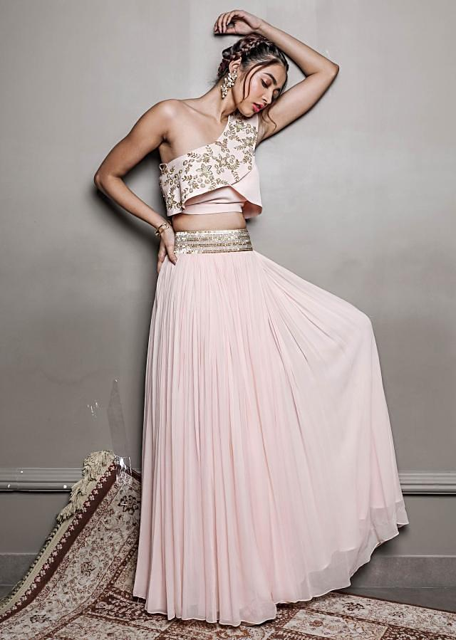 Cornsilk cream one sided sleeves crop top paired with a georgette skirt heavely studed in cut danna on the waistline only on kalki