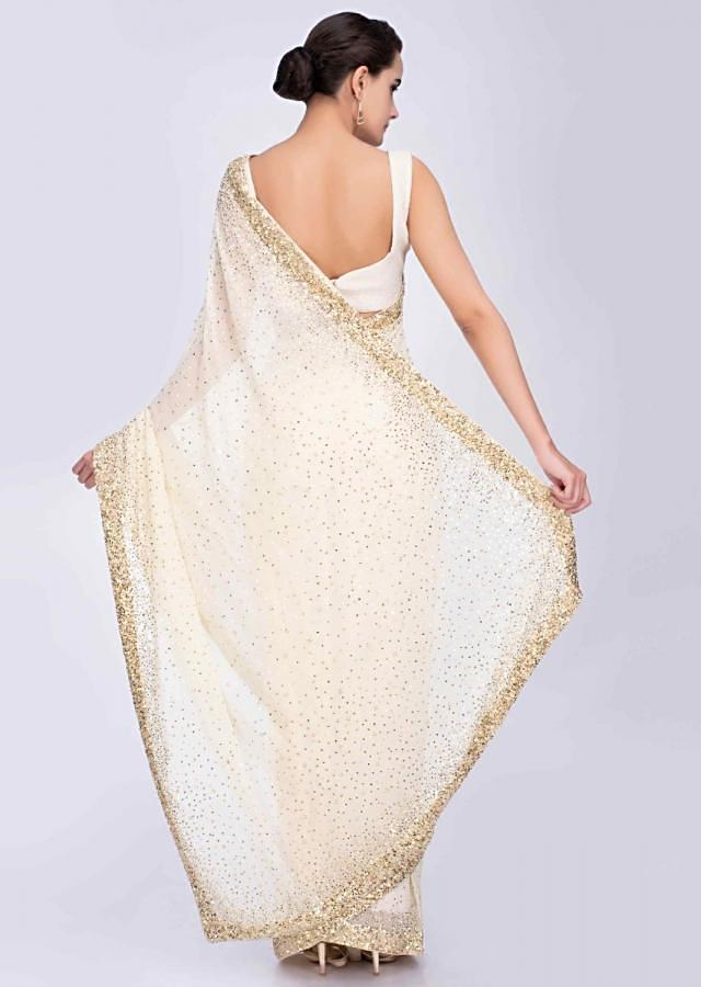 Cream georgette saree with scattered sequins and pearls densily on the border only on Kalki