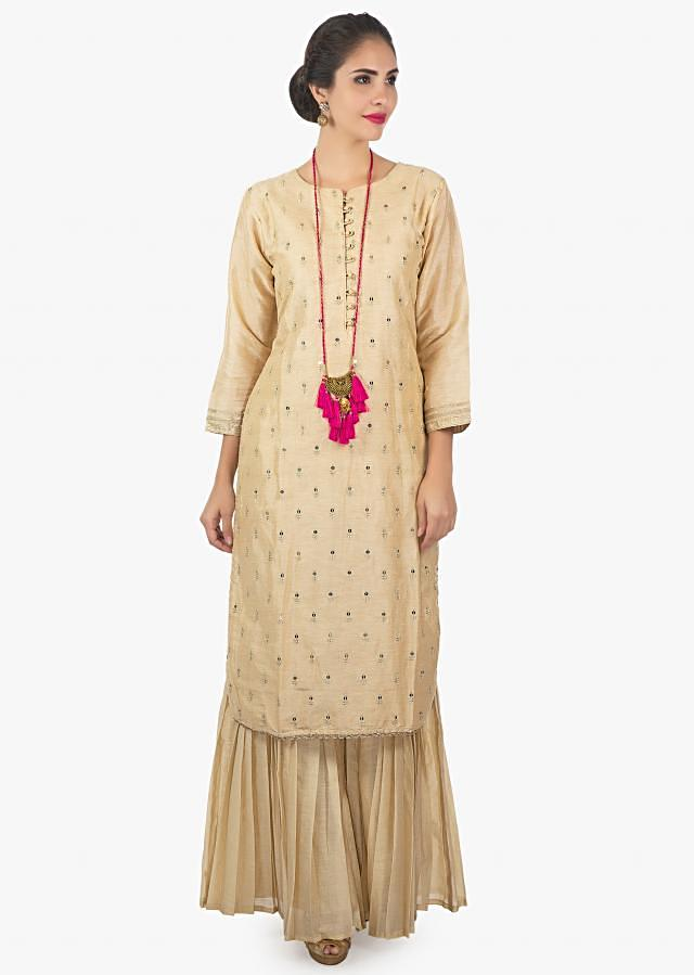 Cream latte sharara set paired with a rani pink brocade dupatta only on Kalki