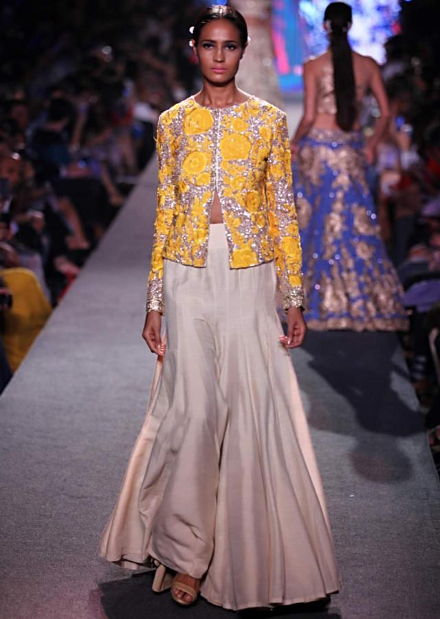 Model walks the ramp in cream lehenga with yellow embroidered blouse for Manish Malhotra Blue Runway collection at Lakme Fashion Week Summer Resort 2015