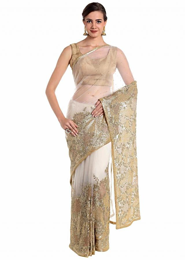 Cream net saree designed with shimmering zari and sequins only on Kalki