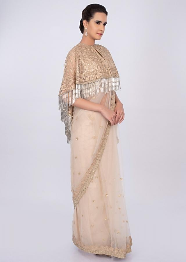 Cream net saree with embroidered  tasseled cape only on kalki