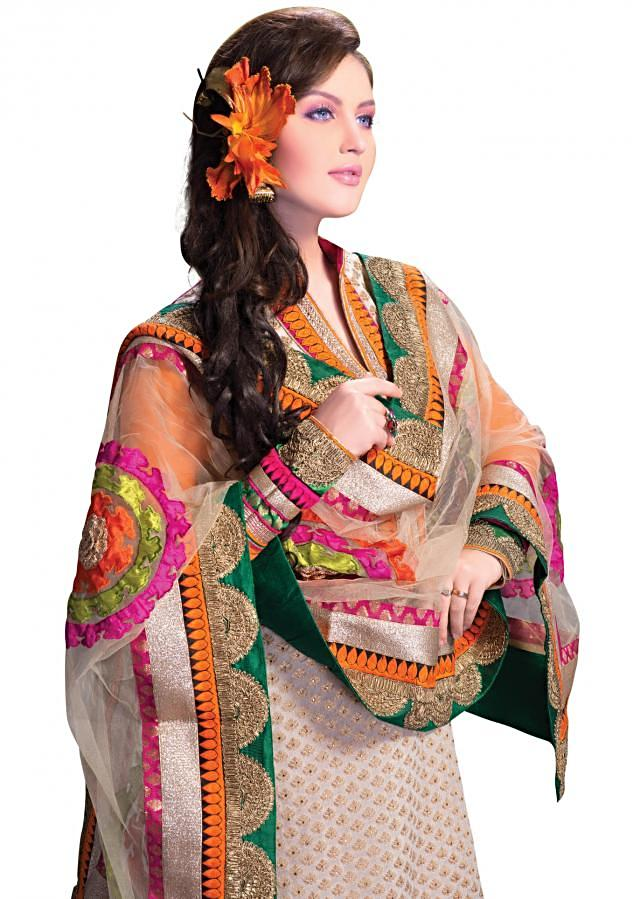 Cream semi stitched brocade suit with machine work borders and embellished with delicate handwork
