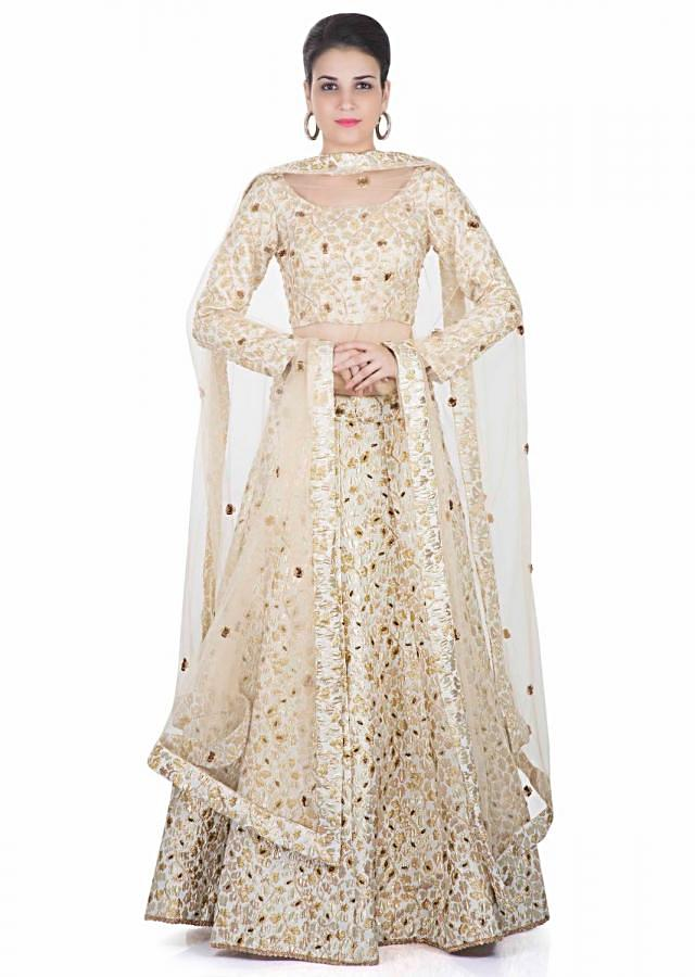 Cream Taffeta Silk Top and Skirt Adorned with Floral Motifs and Net Dupatta only on Kalki