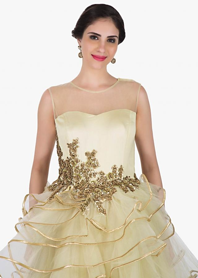 Cream  gown in net is heavily crafted in sequin floral embroidery work only on Kalki