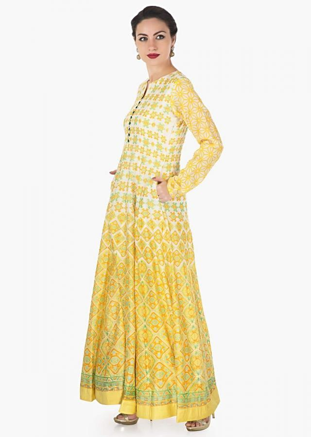 Cream long dress in yellow and green printed butti all over only on Kalki