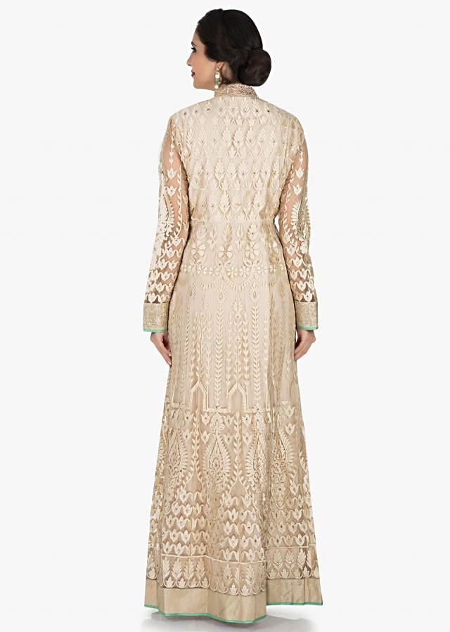 Cream net suit with green dupatta enhanced in resham embroidery only on Kalki