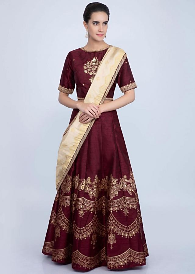Dark maroon weaved lehenga with embroidered blouse and cream dupatta only on Kalki