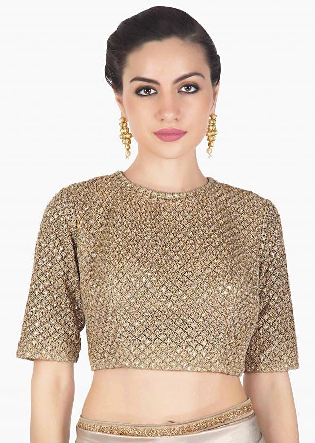 Dull gold shimmer saree matched with embroidered blouse only on Kalki