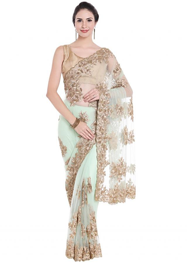 Featuring mint blue net saree in zari butti and border only on Kalki