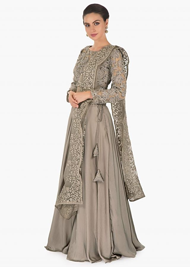 Fossil grey net lehenga matched with a bateau neck along with fossil grey net blouse and a satin crepe net tissue dupatta only on kalki