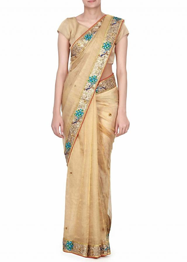 Vivacious ‌gold saree adorn in peacock motif embroidery only on Kalki