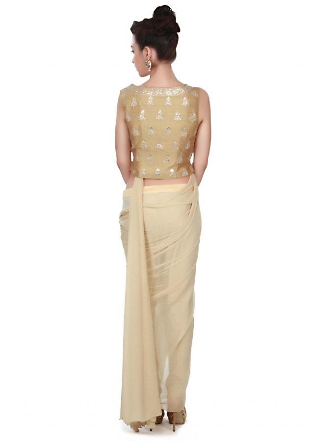 Gold saree gown adorn in pre stitched drape and jacket blouse only on Kalki