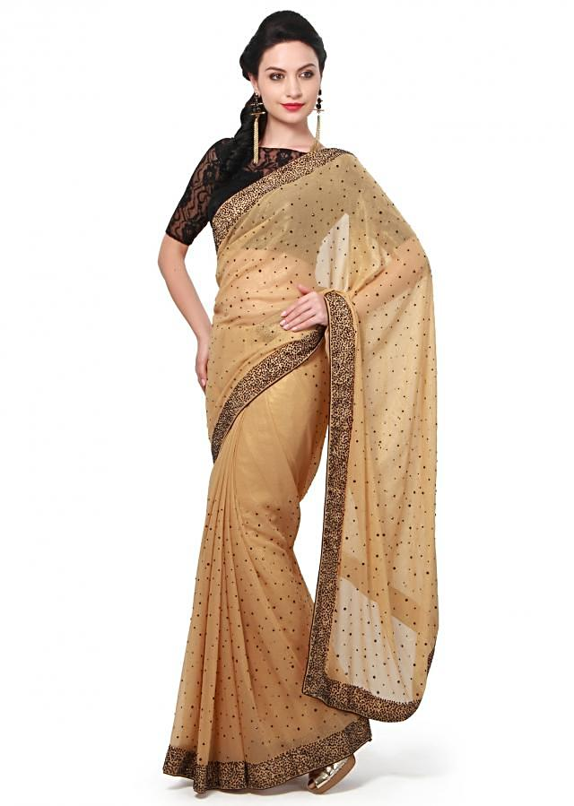 Gold saree featuring in shimmer. Its enhanced in black kundan all over. Matched with ready blouse in black Chantilly lace.