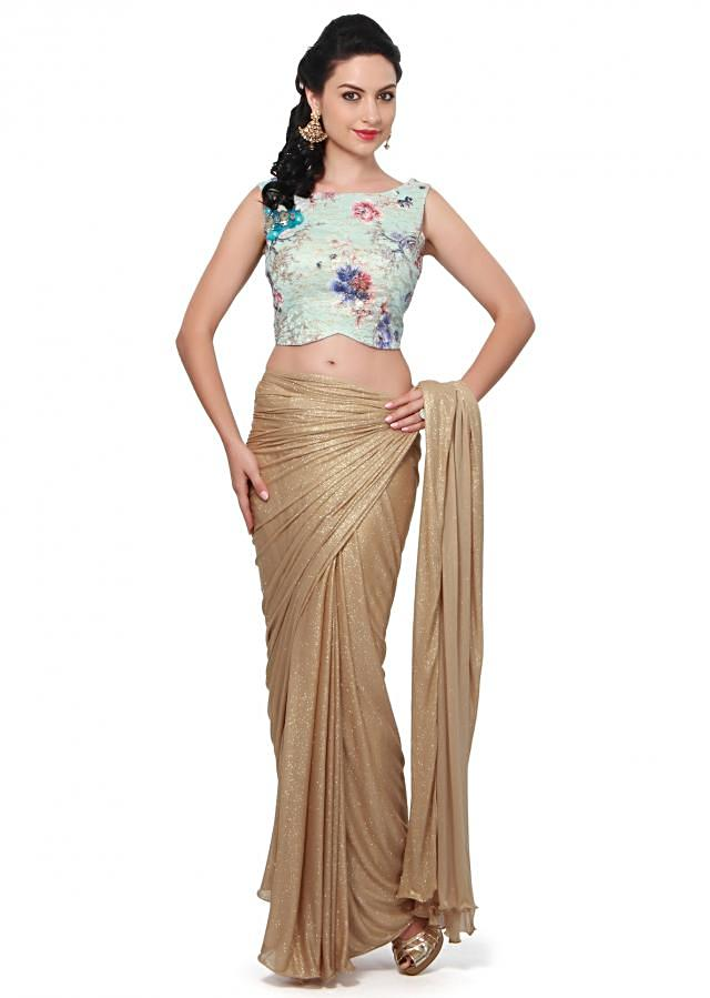 Glazing gold saree in lycra. Matched with sky blue ready blouse in floral print and stone embroidered butti.