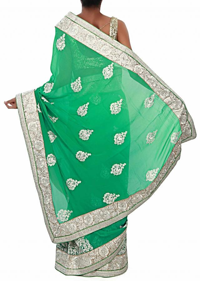 Green saree adorn in silver embroidered butti and border only on Kalki