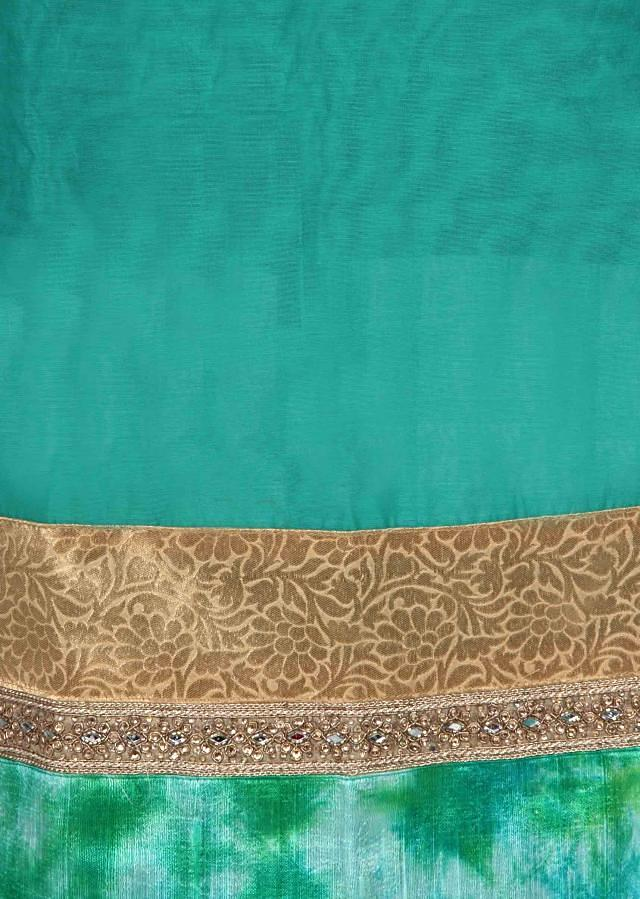 Green unstitched suit features with highlighted hem line only on Kalki