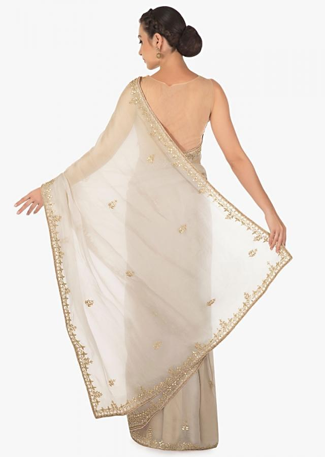 Grey tissue silk saree in gotta patch and motif embroidery only on Kalki