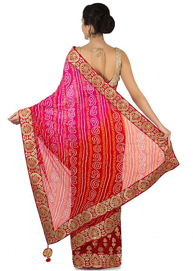 Half and half bandhani saree in rani pink and red with gotta patch border only on Kalki