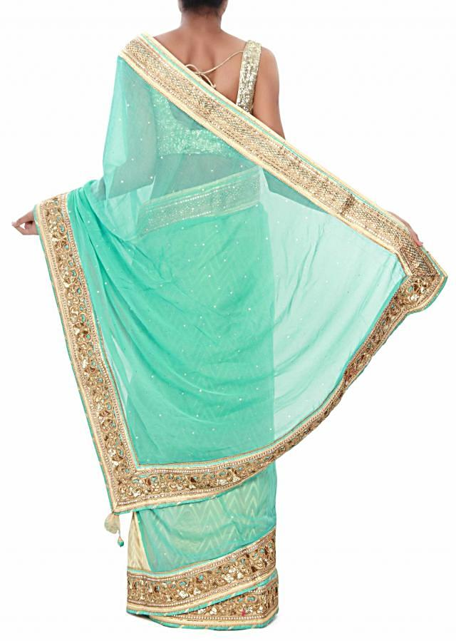 Half and half saree in beige and sea blue adorn in cut work border only on Kalki