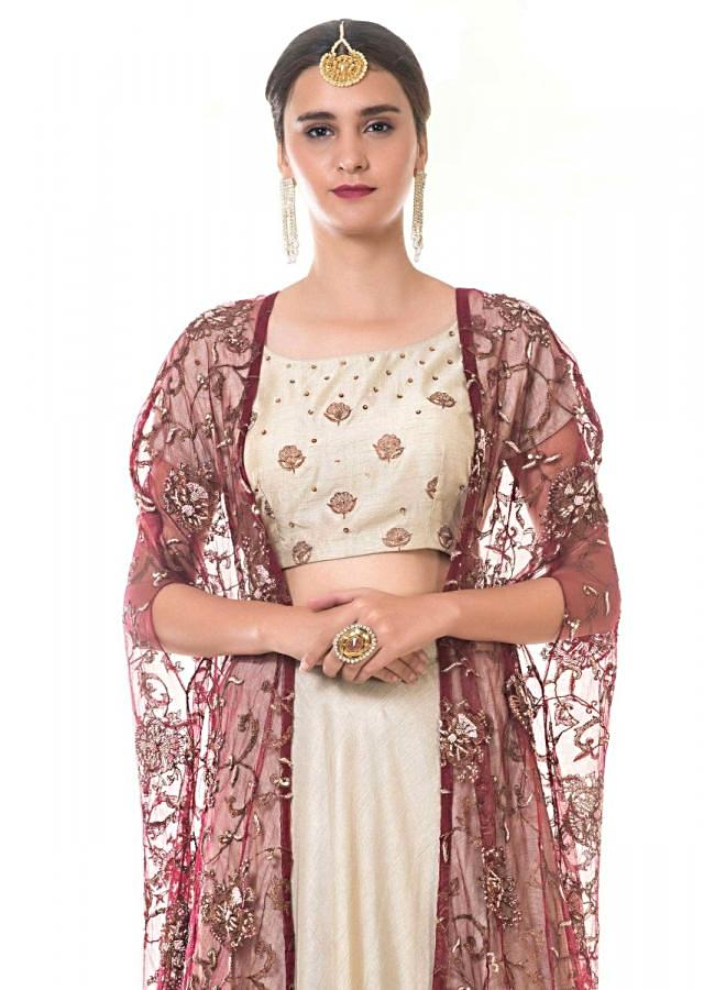 Cream Blouse And Ruffle Tier Lehenga Set With A Heavy Embroidered Tasselled Cape Online - Kalki Fashion