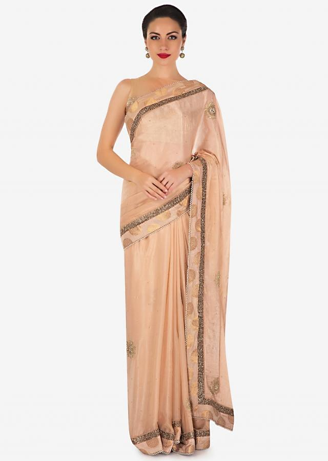Light peach saree in satin with embroidered butti and border only on Kalki