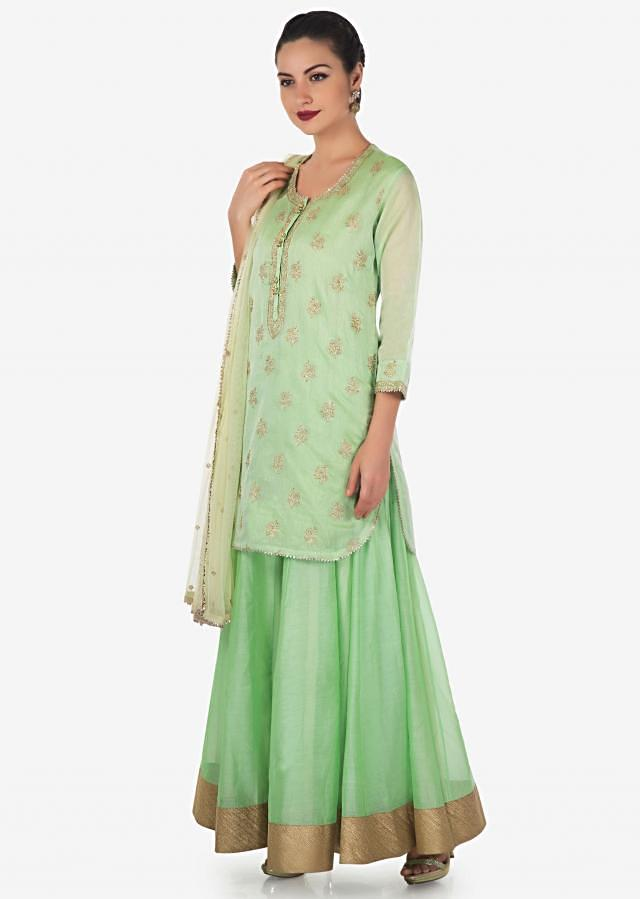 Light pista green straight suit matched with skirt in resham embroidered placket and butti only on Kalki