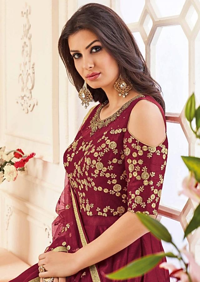 Maroon anarkali suit in raw silk with cold shoulder in zari and kundan embroidered