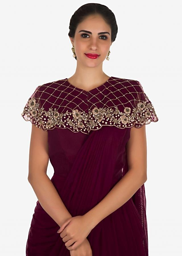 Maroon saree gown in net with a fancy cape adorn in zardosi and moti embroidered work only on Kalki