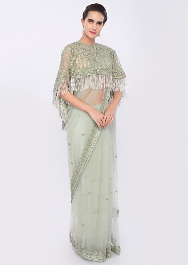 Mint green embroidered net saree complemented with tasseled net cape only on Kalki