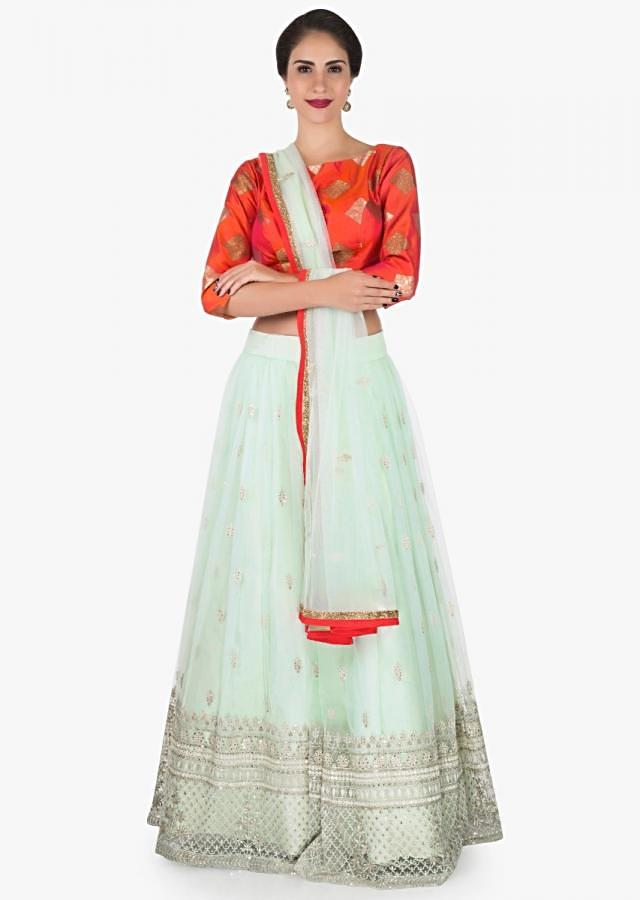 Mint blue lehenga with a orange brocade silk blouse embellished in thread work only on Kalki