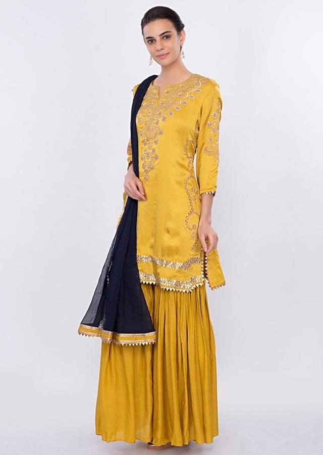 Mustard embroidered sharara suit set with contrasting navy blue dupatta only on Kalki