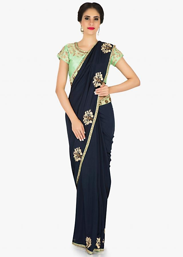 Navy blue saree in raw silk with pista green blouse adorned in zari and thread butti work only on Kalki