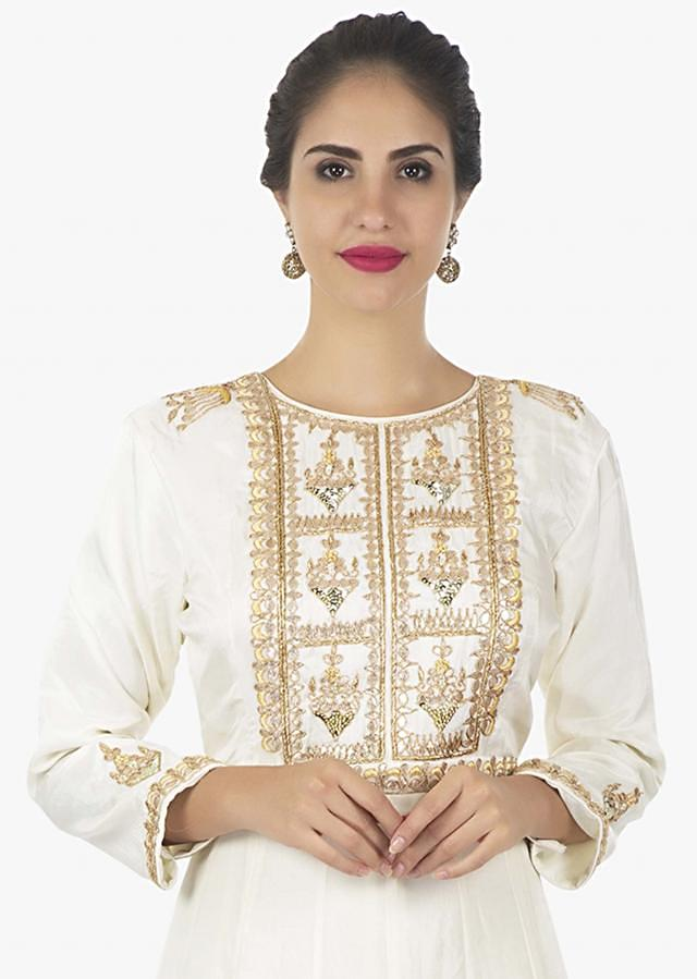 Off white anarkali dress paired with a weaved yellow dupatta  only on kalki