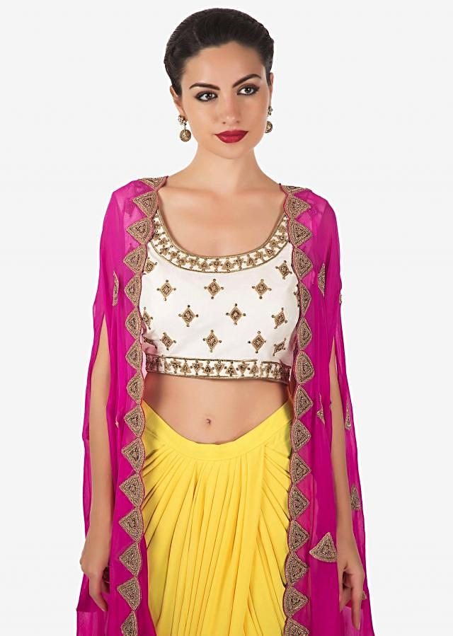 Off white crop top and yellow cowl drape skirt matched with rani pink embroidered jacket only on Kalki