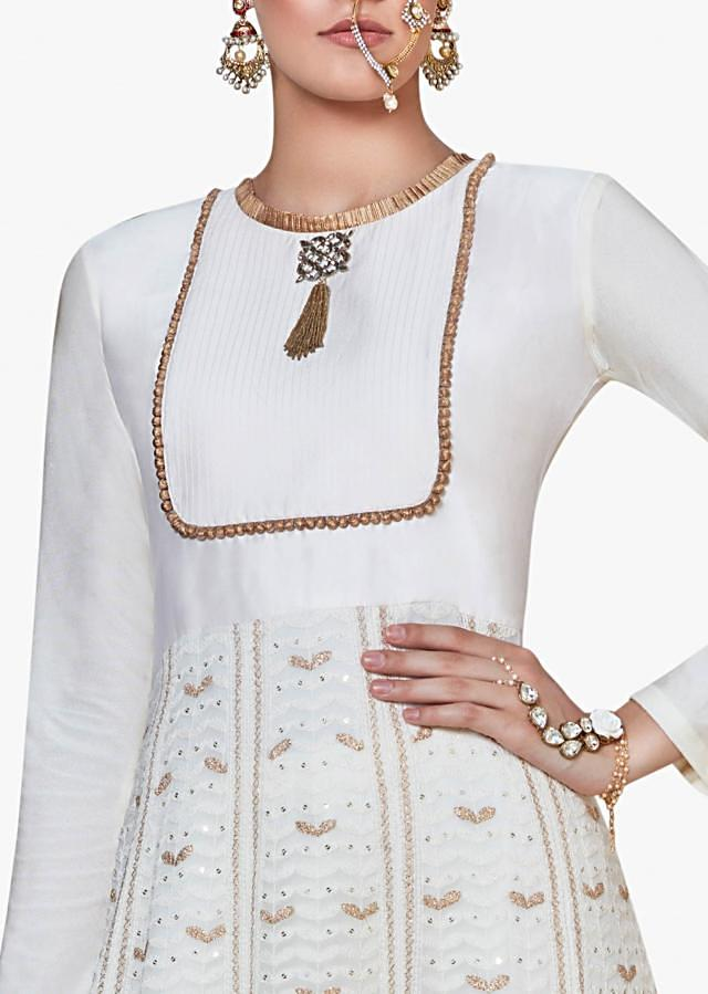 Off-white anarkali suit enhanced in Lucknowi Thread work with fancy stone and tassel design