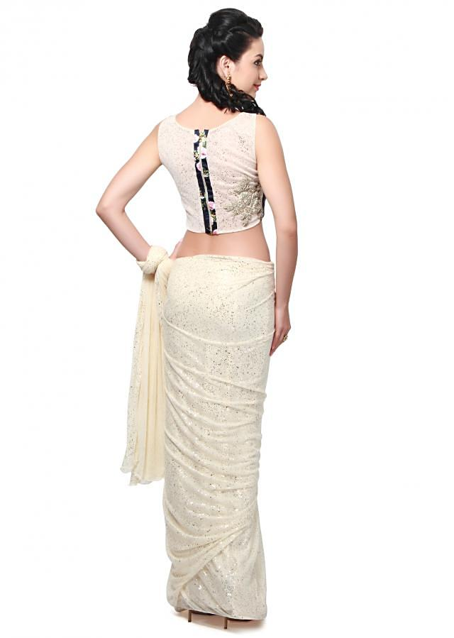 Off white saree featuring in shimmer lycra. Its matched with navy blue ready blouse enhanced in floral print and zari embroidered butti.