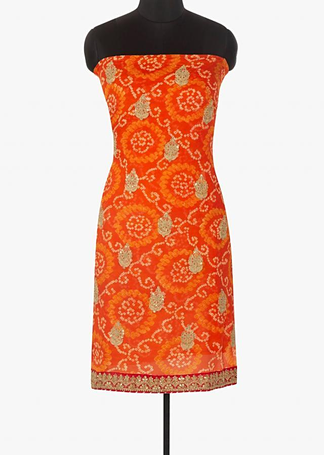 Orange unstitched suit in bandhani georgette with embroidered hem line only on Kalki