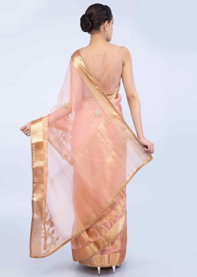 Peach organza saree with golden weaved border in human and animal motif only on Kalki