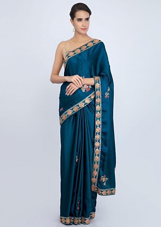 Peacock blue satin saree with multi color resham embroidered butti in floral motif only on Kalki