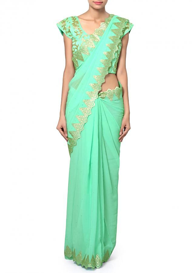 Pista green saree featuring in georgette. Enhanced in applique lace border.matched with ready blouse in raw silk adorn in kardana embroidery.