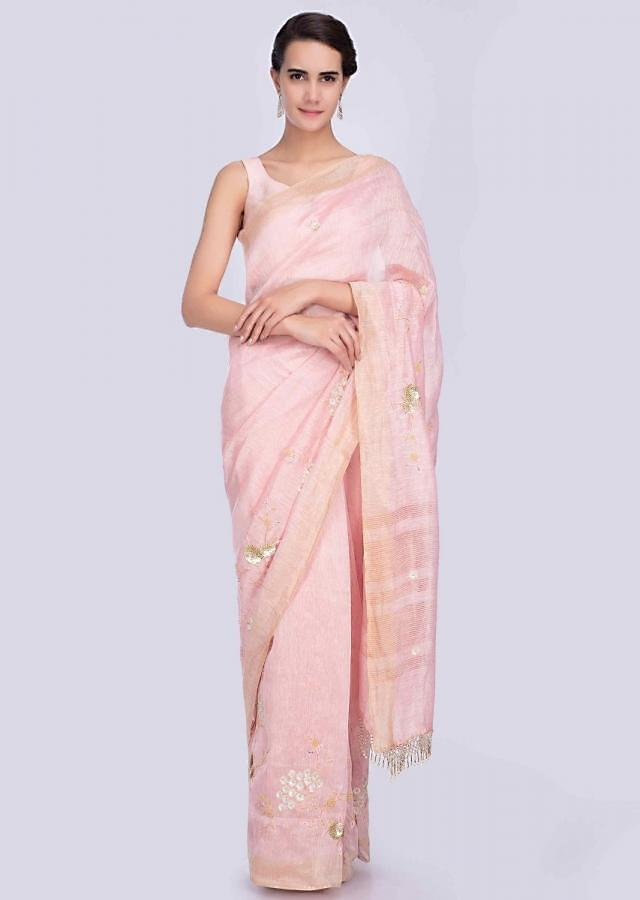 Powder pink linen saree adorn with hand embellished butti and border only on Kalki