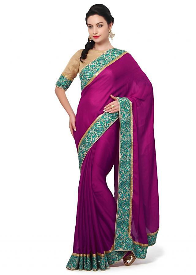 Magenta saree featuring in sati. Border is embellished in resham in paisley motif. Matched with ready blouse in gold shimmer georgette.